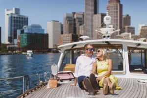couple smiling sitting on deck with boston in view