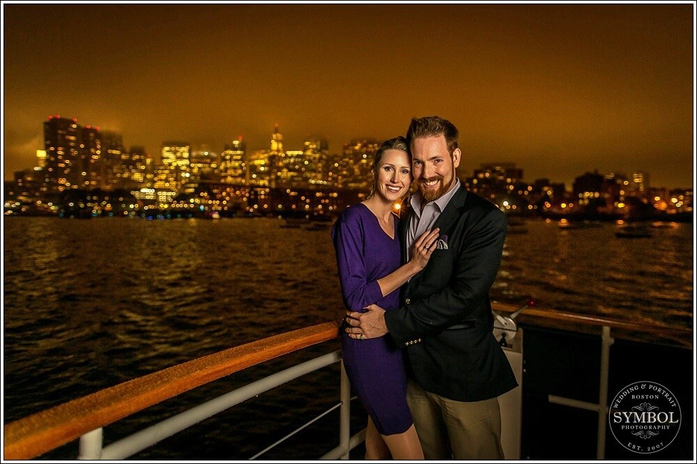 couple smiling on a boat cruise at night with boston in view