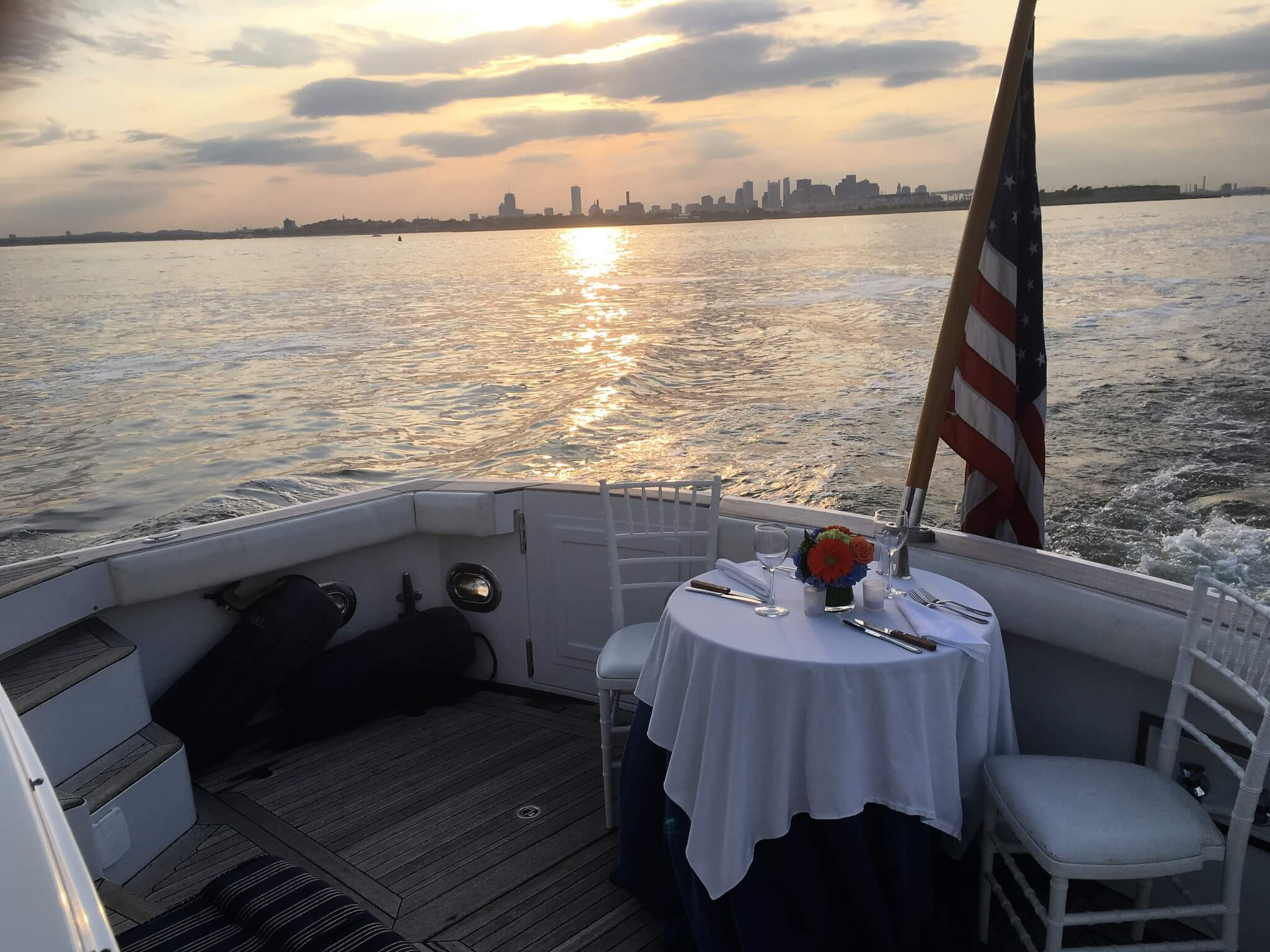 dining table for two set on boat with boston skyline