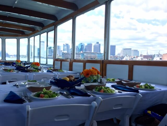 tables set on board vessel with boston skyline in view