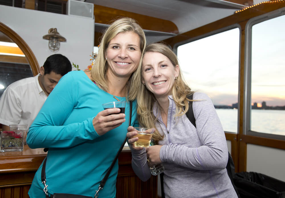 two women posing with drinks on board ship