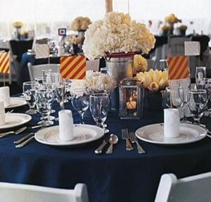 a set table on navy table cloth with white floral arrangement