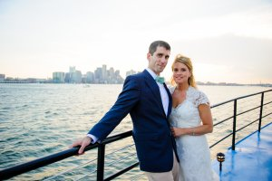 bride and groom with boston across the water