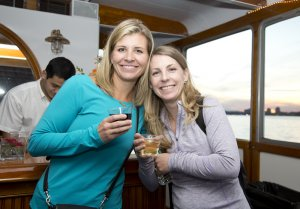 two women with drinks in hand aboard private charter