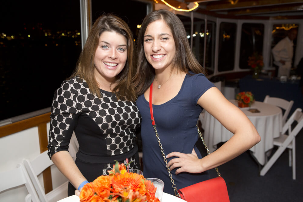 two women posing on board a boat cruise event