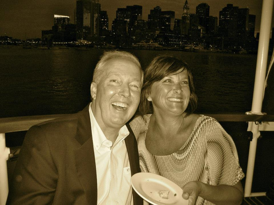couple smiling on board ship with boston in the background at night
