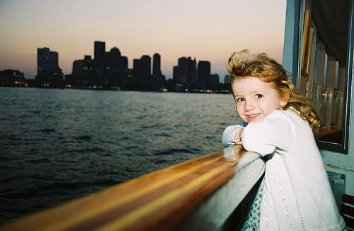 child looking at the boston skyline from boat at dusk