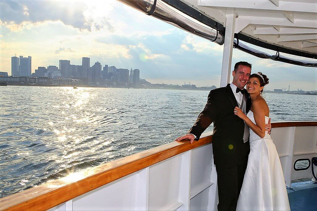bride and groom standing on ship with boston in view