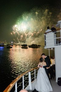 bride and groom kissing in front of fireworks on a ship