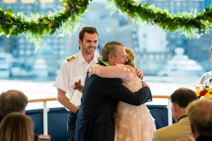 bride and groom hugging at altar on ship