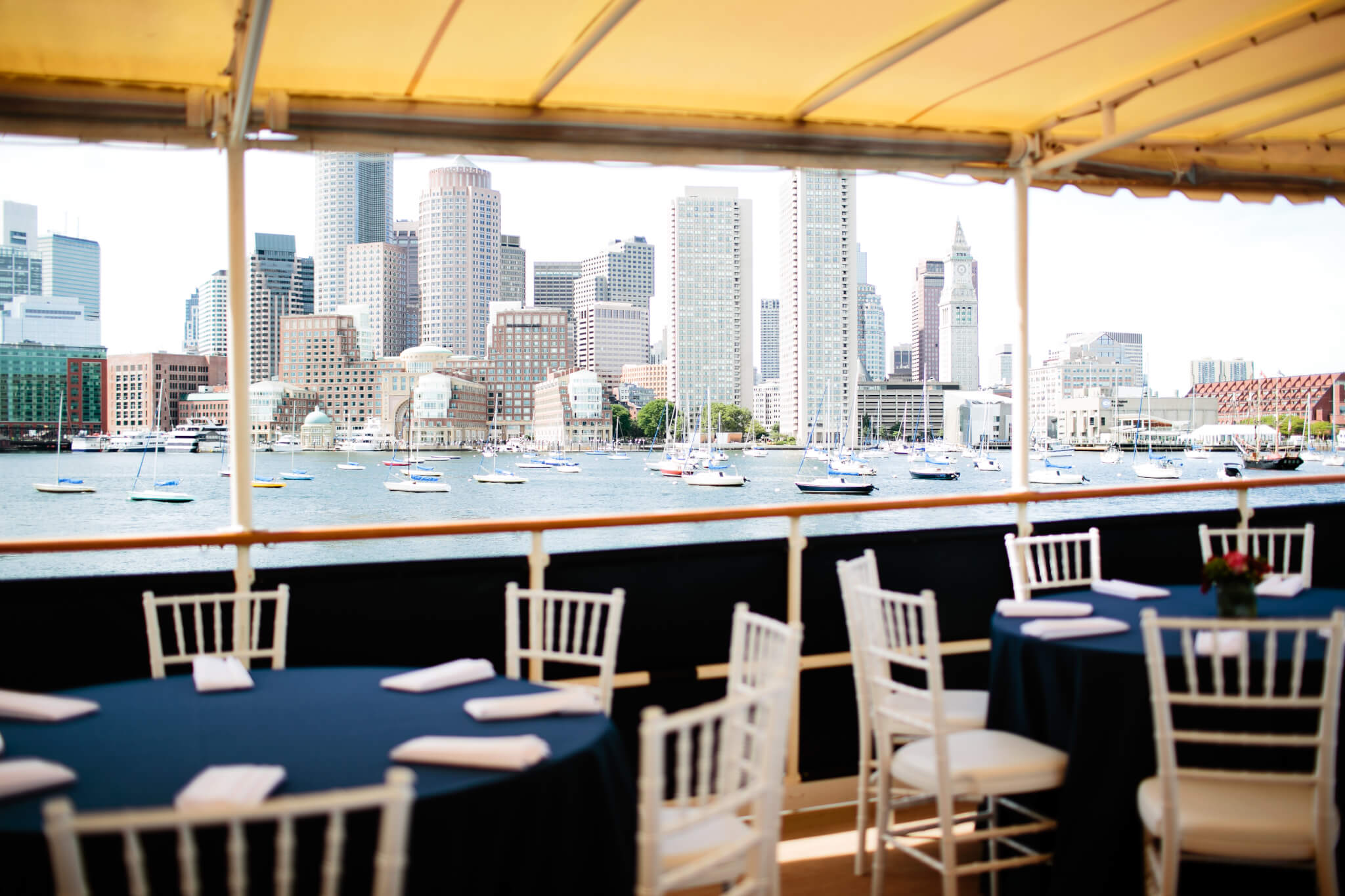 dining area aboard vessel with boston in the background