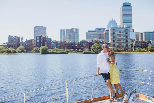 couple posing on board cruise with boston in the background