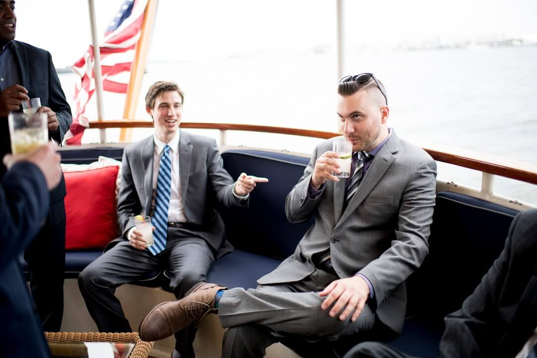 men drinking and talking in suits on boat
