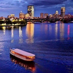 a charles riverboat vessel cruising the water towards the boston skyline