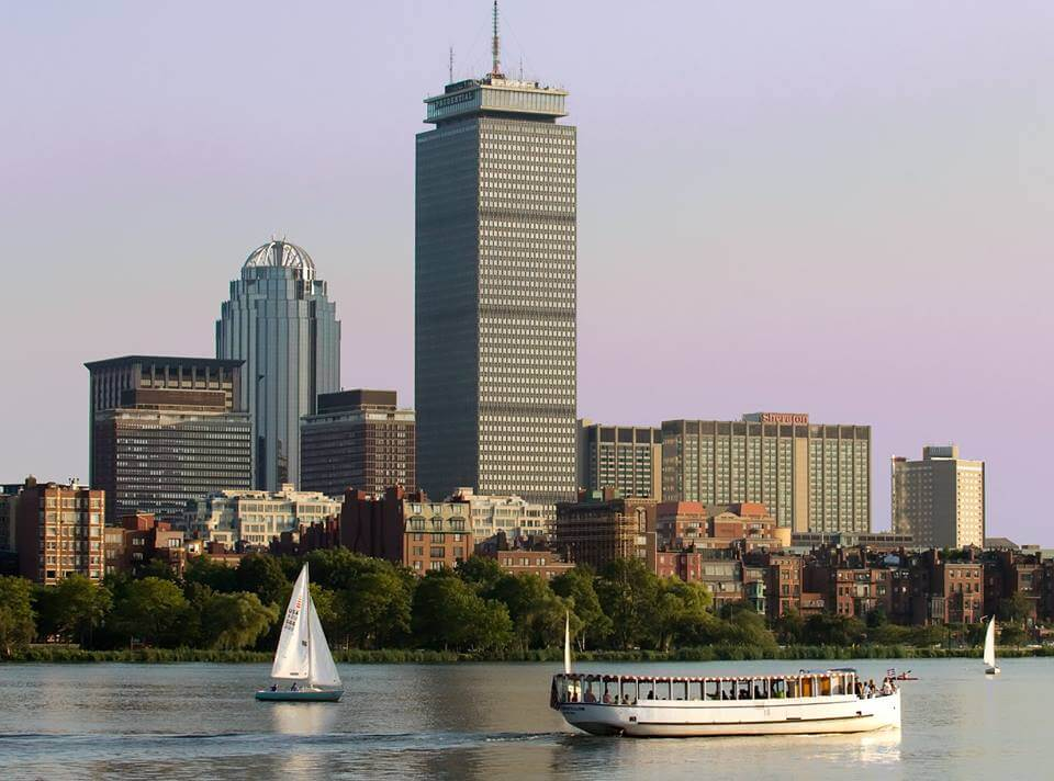 boston skyline from the water with a charles riverboat company tour and sailboat in the water