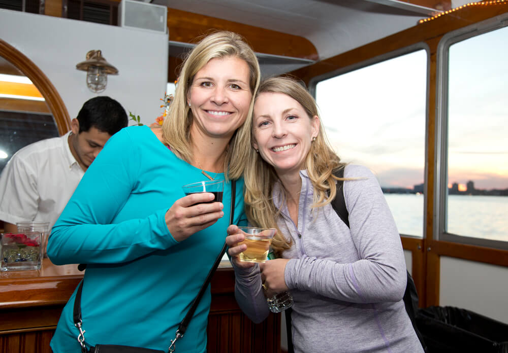 two women holding drinks at a vessel's bar
