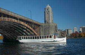 a charles riverboat vessel cruising under a bridge