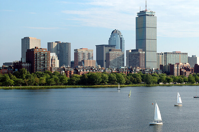 boston skyline across the water with sailboats